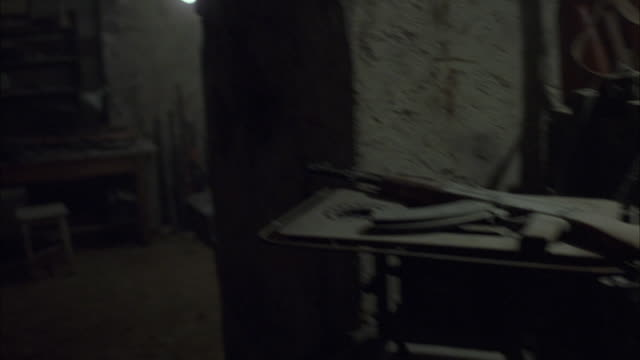 WIDE ANGLE OF BUNKER OR BUILDING INTERIOR. BUILDING HAS OLD, CHIPPED WALLS AND EXPOSED LIGHT BULBS.
