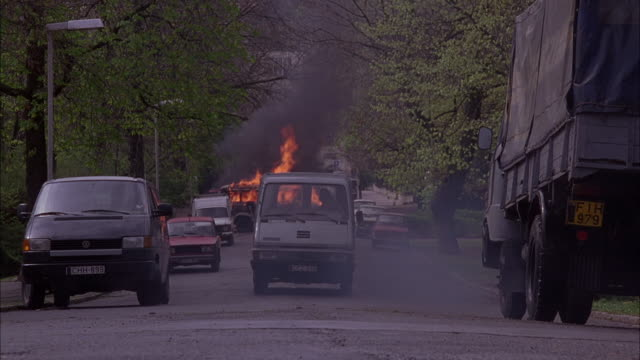 WIDE ANGLE OF BLUE VAN REVERSING DOWN EUROPEAN STREET. MILITARY TRUCK IS ON FIRE IN THE MIDDLE OF THE STREET. FLAMES AND SMOKE SHOOT OUT OF THE TRUCK, WHICH IS BLOCKING THE ROAD.