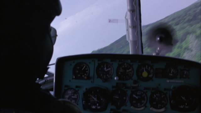 medium angle of military helicopter cockpit, pilot seen from behind, gauges. flying over trees, forest, fields. - military helicopter stock videos and b-roll footage