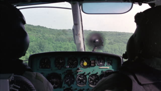 MEDIUM ANGLE OF MILITARY HELICOPTER COCKPIT, PILOT SEEN FROM BEHIND, GAUGES. FLYING OVER TREES, FOREST, FIELDS.