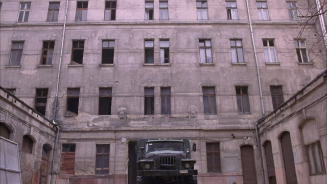 MEDIUM ANGLE OF MILITARY TRUCK APPROACHING POV. MILITARY TRUCK ENCLOSED IN IN COURTYARD OF TALL BUILDING, COULD BE A MILITARY COMPOUND OR BASE. VEHICLE SPEEDS UP, COULD BE USED AS A POV OF ONCOMING CRASH.