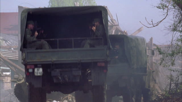 wide angle of two military vehicles driving through a war or fighting zone. military personnel with rifles are sitting in military trucks. see tank on left side of road and remains of a building that was knocked down, or blown up. - 2002年点の映像素材/bロール