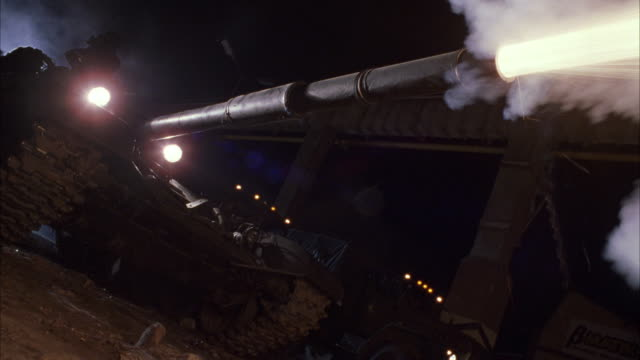 MEDIUM ANGLE OF MILITARY TANK TURNING LIGHTS ON AND FIRING CANON OR GUN. SEE SMOKE AND FLAME FROM END OF GUN. MILITARY CARGO VEHICLE DRIVE BEHIND TANK. TANK TURNS LIGHTS OFF. COULD BE ARMY.