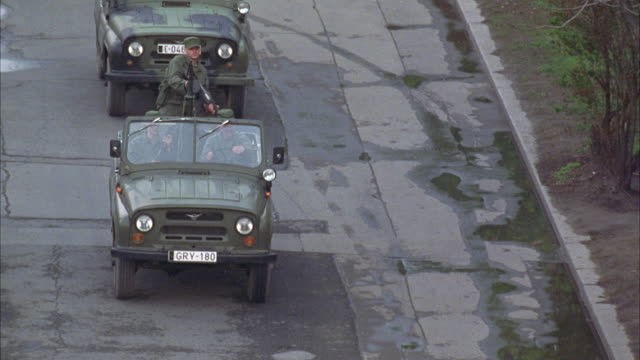 medium angle of jeeps with soldier machine gunner and mercedes car.  vehicles drive through street, arrive at what could be embassy or army base building. soldiers, guards. - mercedes benz stock videos and b-roll footage