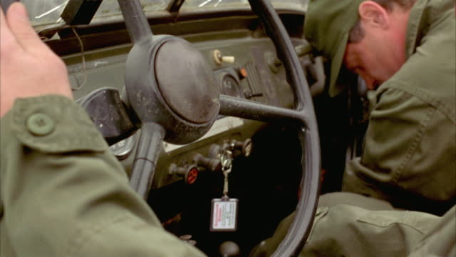 MEDIUM ANGLE OF MILITARY SOLDIERS OR MEN DRIVING IN MILITARY VEHICLE OR TRUCK AND GETTING SHOT AND KILLED AFTER GUNFIRE. SEE DRIVER'S FOOT PUSH GAS PEDAL AFTER HE DIES. DEATHS.