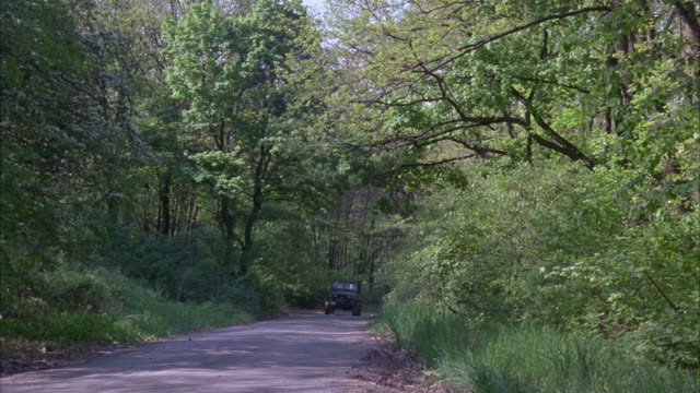 vídeos de stock e filmes b-roll de medium angle of road through woods or forest. jeep driven by man in fatigues and black sedan drive past, turn off onto side road. - jeep