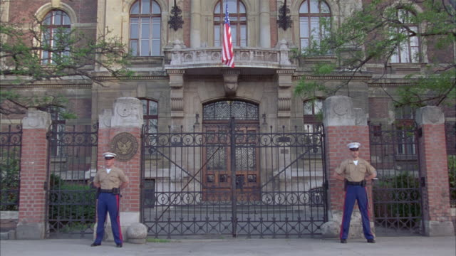 zoom in of embassy or military base. building bearing american flag, armed marines guard gate. - embassy stock videos and b-roll footage