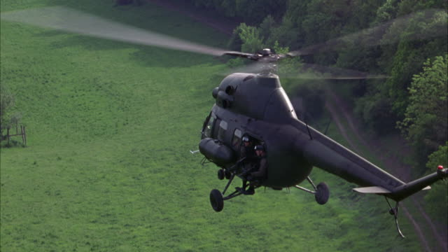 hand held shot of a polish mi-2 military helicopter hovering above a green forest. several soldiers lean out of the side door. - military helicopter stock videos and b-roll footage
