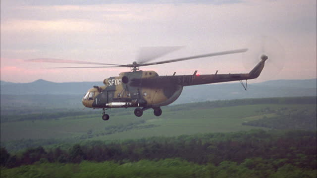 hand held shot of a polish mi-8 military helicopter flying above a green forest.  painted camo or camouflage with bombs or missiles along the side.  the dusk sky glows pink.  could be dawn. - military helicopter stock videos and b-roll footage