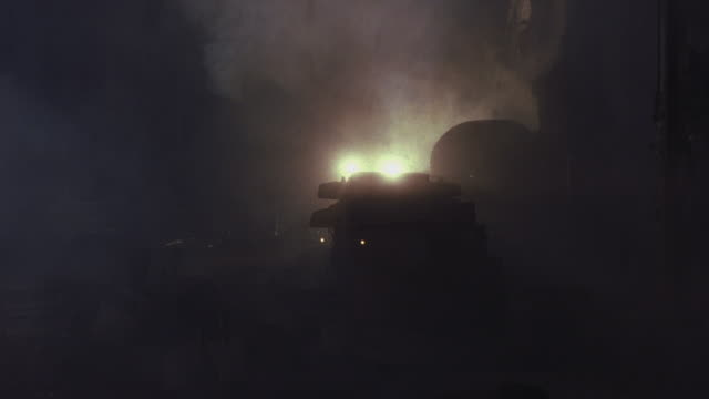 vidéos et rushes de wide angle of military tank with bright headlights driving toward camera through industrial area between buildings on battlefield. troops or soldiers walk near tank. see fog, smoke or haze. - budapest
