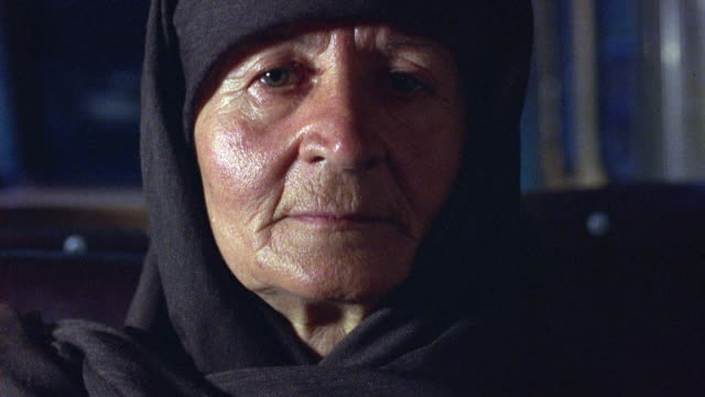 CLOSE ANGLE OF OLDER WOMAN'S FACE  AS SHE STARES STRAIGHT AHEAD. BUS BOUNCES AS EXPRESSIONLESS WOMAN SITS WEARING HEADSCARF OR SHAWL.
