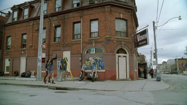 """WIDE ANGLE OF LOWER CLASS STREET CORNER AND BRICK BUILDING WITH """"VENOM LIVE MUSIC"""" SIGN. PAY PHONES VISIBLE AS PEDESTRIANS WALK BY."""