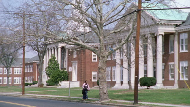 pan left to right of cars crossing driving in front of a large brick building.  could be an old hospital, school, college, or university. - new jersey stock-videos und b-roll-filmmaterial
