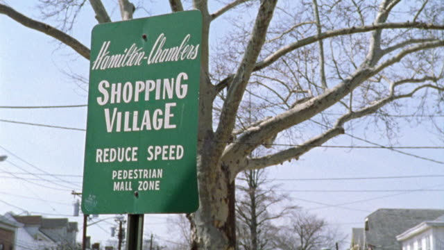 """pan left to right across a commercial area. a sign reads """"hamilton-chambers shopping village"""". several two story brick buildings and shops.  a traditional looking small town main street. - targa con nome della via video stock e b–roll"""