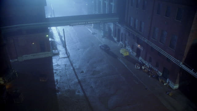 "high angle down of ""gooderham & worts limited"" warehouses or factories. car being chased by suv speeds into alleys below. fog. - gasse stock-videos und b-roll-filmmaterial"