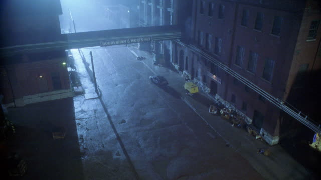HIGH ANGLE DOWN OF 'GOODERHAM & WORTS LIMITED' WAREHOUSES OR FACTORIES. CAR BEING CHASED BY SUV SPEEDS INTO ALLEYS BELOW. FOG.