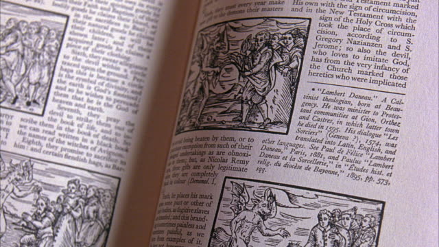 close angle of pages being turned in book with medieval illustrations, drawings and etchings of religious demons and devils. some text is in latin and english. see pile of books in background. could be bookstore. - medieval stock videos & royalty-free footage