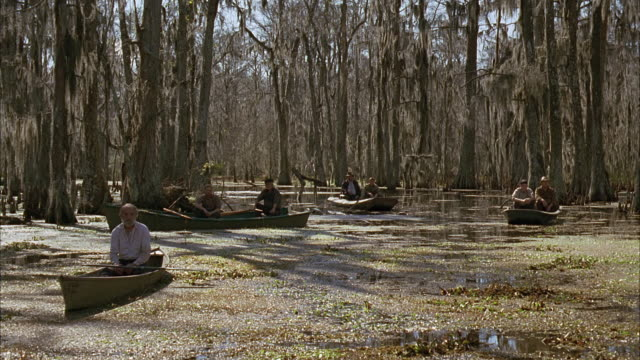 stockvideo's en b-roll-footage met wide angle of swamp land, water with leaves floating, men in boats or canoes. autumn. plants, bare trees. - men