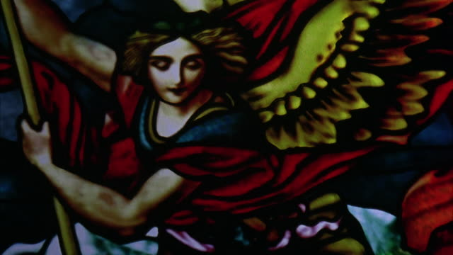 vídeos y material grabado en eventos de stock de close angle shows detail of colorful stained glass window. angel with wings, clothing and staff is depicted. could be saint michael the archangel. possibly from church window. religious. - vidriera de colores