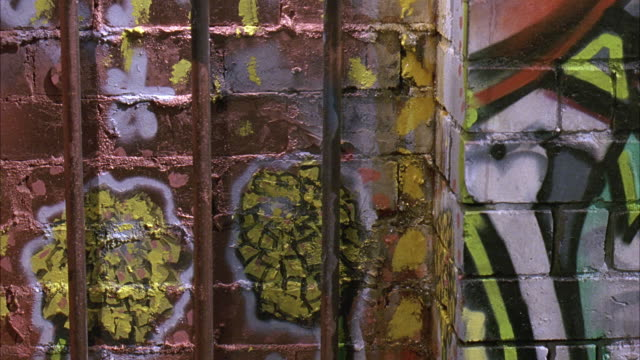 close angle of graffiti and metal bars in rainy alley. camera pans around showing leaking pipes, rain gutters with water pouring out, puddles and grotesque faces painted on brick buildings. could be used for gang turf. - alley stock videos & royalty-free footage