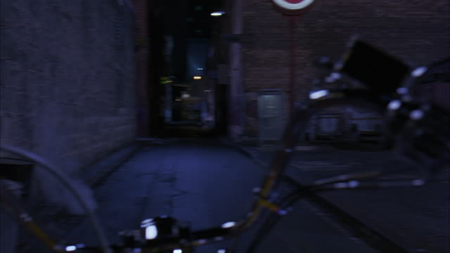 WIDE ANGLE OF STEAMY ALLEY FRAMED BY MOTORCYCLE HANDLEBARS FROM POV OF MOTORCYCLE RIDER. CAMERA PANS LEFT TO RIGHT SEVERAL TIMES TO SHOW HAND OF RIDER