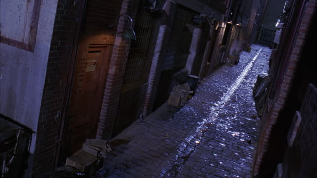 high angle down of dimly lit, steamy alley. alley has boxes, clutter, wood pallets, barred windows, overhead lamps and  doorways. gutter runs down the brick alley. - building entrance stock videos & royalty-free footage