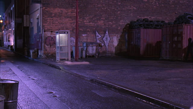 WIDE ANGLE OF ALLEY BETWEEN BRICK BUILDINGS AS BLACK TWO DOOR SEDAN DRIVES PAST, DOWN ALLEY. ALLEY HAS PHONE BOOTH, GRAFFITI AND OIL DRUMS OR BARRELS.