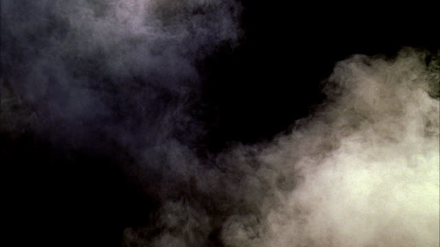 vidéos et rushes de medium angle of smoke, mist or fog swirling against black background. could be night. - brouillard