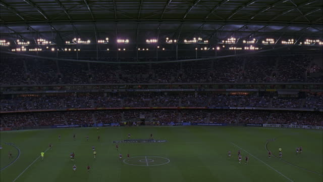 wide angle of melbourne's telstra dome stadium during rugby game. bleachers are filled with crowded with spectators. sports arena playing field, players, advertisement banners and lights visible. retractable roof closed. sports. - tribuna video stock e b–roll