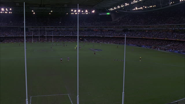 wide angle of melbourne's telstra dome stadium seen from behind goal post during rugby game. bleachers crowded with spectators. - scoring stock videos and b-roll footage