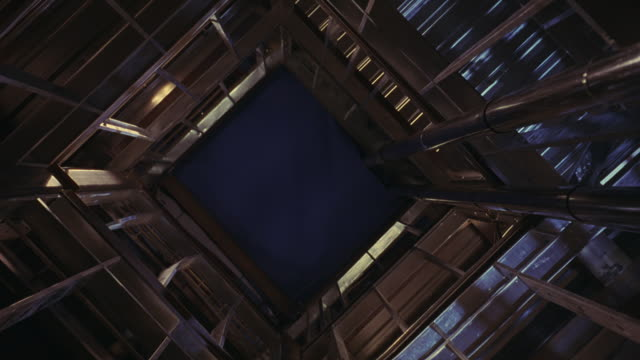 UP ANGLE OF MAYBE AN ELEVATOR SHAFT OR SOME KIND OF CONSTRUCTION SITE.  THE CAMERA SPINS IN A VERTIGO EFFECT.  METAL STEEL RODS LEAD TO A BLUE SCREEN.