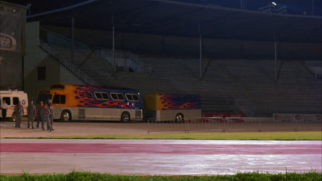 WIDE ANGLE OF STADIUM, ARENA. SEE WORKING CREW, POSSIBLE MECHANICS. BUS AND TRAILER IN BACKGROUND. MOTORCYCLE RIDER SKIDS, SLIDES ACROSS FLOOR RIGHT TO LEFT, AS IF HE WAS JUST THROW FROM A BIKE. COULD BE USED AS RIDING ACCIDENT. STUNTS.