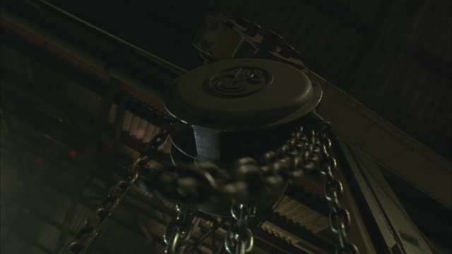 up angle of winch, chain pulley in warehouse. chain moves through pulley as if pulled, one end flying loose.  see steel girders and corrugate roof. could be on crane or tow truck. - flaschenzug stock-videos und b-roll-filmmaterial