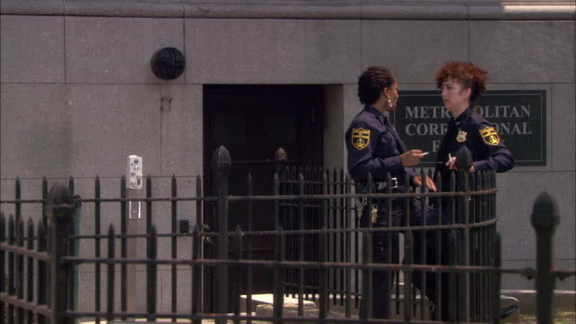 MEDIUM ANGLE OF TWO FEMALE POLICE OFFICERS STANDING IN FRONT OF 'METROPOLITAN CORRECTIONAL FACILITY' SMOKING CIGARETTES.