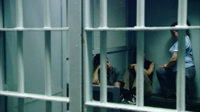 pan left to right inside a women's prison or jail.  looks like a general holding cell.  the prisoners sit and stand close together in the tiny cell.  iron bars in front of them. - women prison stock videos & royalty-free footage