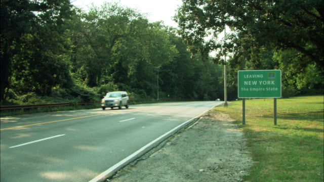 """vídeos y material grabado en eventos de stock de wide angle of interstate highway. """"leaving new york the empire state"""" sign visible at edge of road. cars drive on road towards pov into new york state. trees line highway road to left. freeways. borders. - autopista interestatal"""