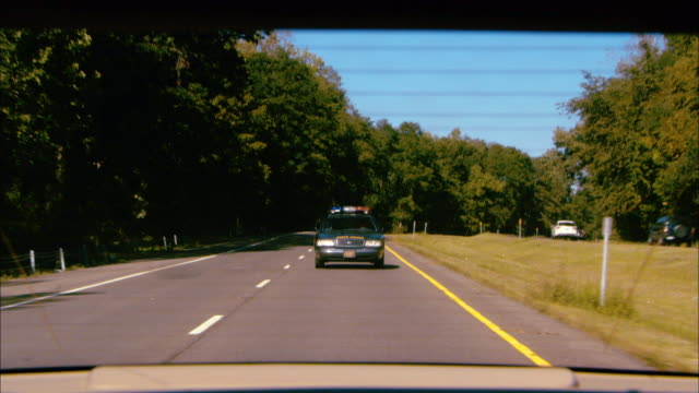 """WIDE ANGLE DRIVING POV STRAIGHT BACK ON HIGHWAY OR FREEWAY. """"STATE POLICE"""" CAR DRIVES BEHIND CAR AND TURNS ON FLASHING LIGHTS AND DRIVES LEFT TO SIDE OF CAR TO PULL CAR OVER."""