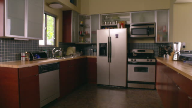 wide angle of kitchen with modern stainless steel appliances. side-by-side fridge with water dispenser. range oven or stove, blender, dish washer, microwave. linoleum flooring. - refrigerator stock videos and b-roll footage