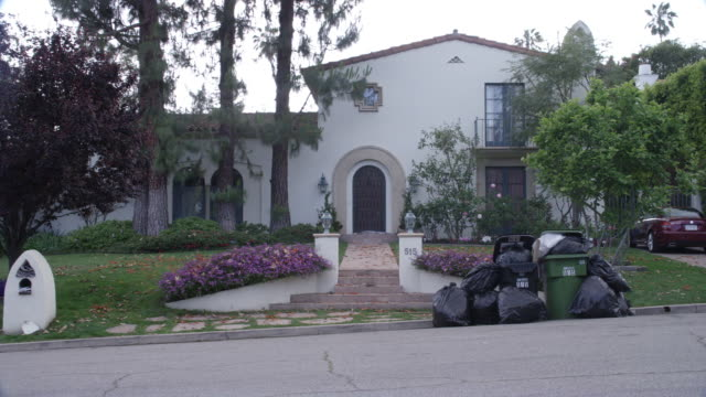 ZOOM IN ON FRONT DOOR OR ENTRANCE TO MIDDLE TO UPPER CLASS SPANISH-STYLE TWO STORY HOUSE. RED TILE ROOFS. FLOWERS, TREES, BUSHES AND SHRUBS IN FRONT YARD OR GARDEN. GRASS LAWN. AUTUMN LEAVES ON GROUND. OVERFLOWING TRASH OR GARBAGE CANS ON CURB.