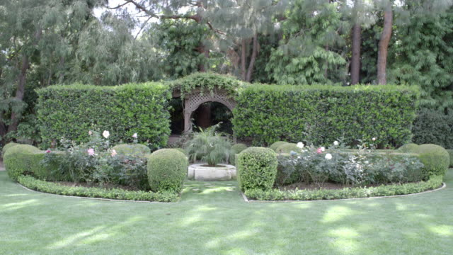 wide angle of upper class garden with pruned hedges, shrubs or bushes. grass lawn and tress. roses. gazebo. - gazebo stock videos & royalty-free footage