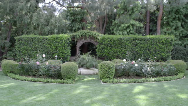 WIDE ANGLE OF UPPER CLASS GARDEN WITH PRUNED HEDGES, SHRUBS OR BUSHES. GRASS LAWN AND TRESS. ROSES. GAZEBO.