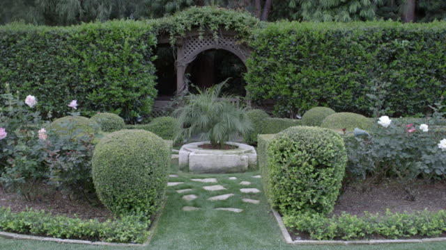 vídeos de stock, filmes e b-roll de pan left to right of upper class garden with pruned hedges, shrubs or bushes. grass lawn and tress. roses. gazebo. small pond. - gazebo