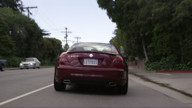tracking shot of mercedes slk 350 car or sedan driving on city streets, sunset blvd near brentwood. upper class neighborhood or suburbs. license plate reads letitgo1. - brentwood los angeles stock videos & royalty-free footage
