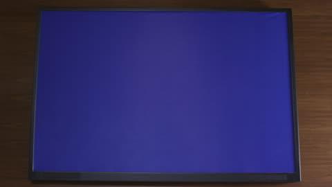 vídeos de stock, filmes e b-roll de close angle of digital display screen on wooden desk. could be tablet computer or laptop. burn-in. - sinalização digital