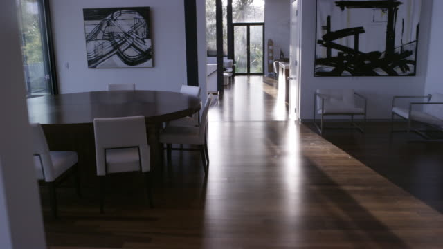 stockvideo's en b-roll-footage met wide angle moving pov through upper class house from living room to kitchen. hardwood floors. art on walls. modern furniture and decor. - houten vloer