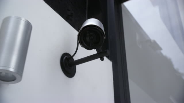 ZOOM IN ON SECURITY OR SURVEILLANCE CAMERA MOUNTED ON WALL. LENS. COULD BE IN OFFICE BUILDING OR MUSEUM.
