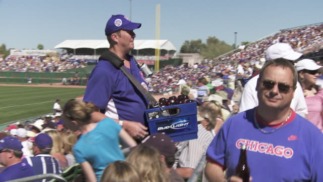 medium angle man or vendor selling beer during chicago cubs baseball game at wrigley field. baseball players on field in bg. spectators in bleachers. - bleachers stock videos and b-roll footage