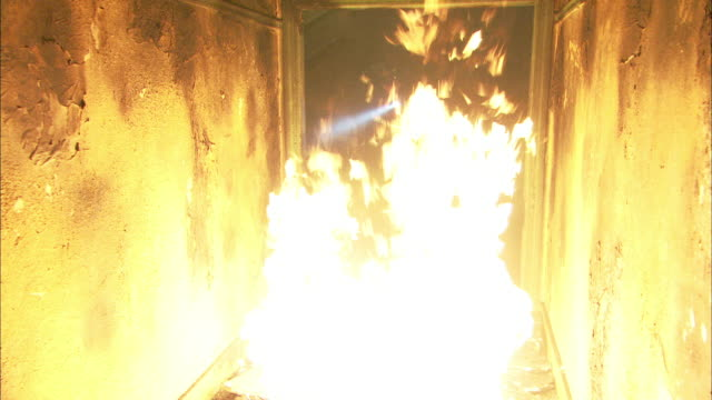 medium angle of new york fire department firefighter jumping over fire or flames in burning apartment building. hallway. - fire natural phenomenon stock videos and b-roll footage