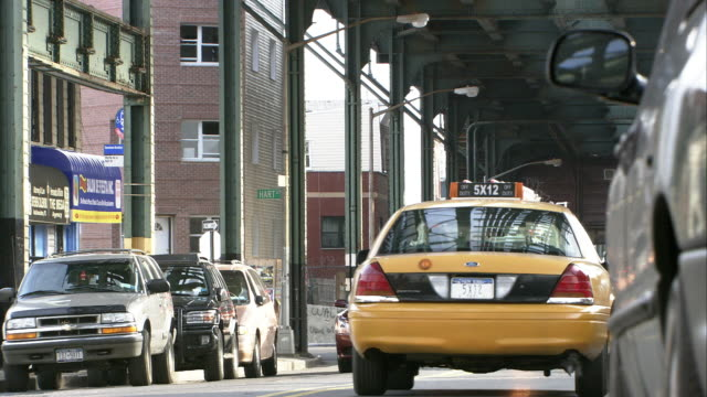 CLOSE ANGLE OF CARS AND TAXIS DRIVING ON NEW YORK CITY STREET UNDER TRAIN BRIDGE OR RAILROAD TRACKS. GRAFFITI ON WALLS. SHOPS AND STOREFRONTS.