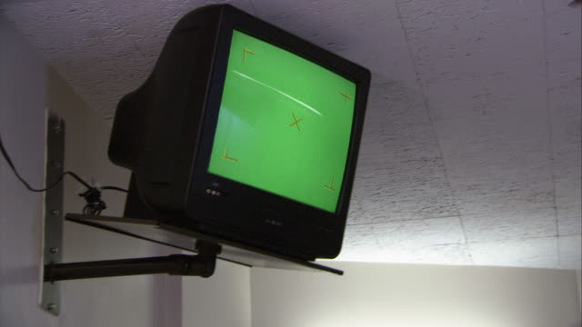 UP ANGLE OF TELEVISION SET ANCHORED TO WALL IN DOCTOR'S OFFICE OR HOSPITAL ROOM. WOULD BE WAITING ROOM. GREEN SCREEN.